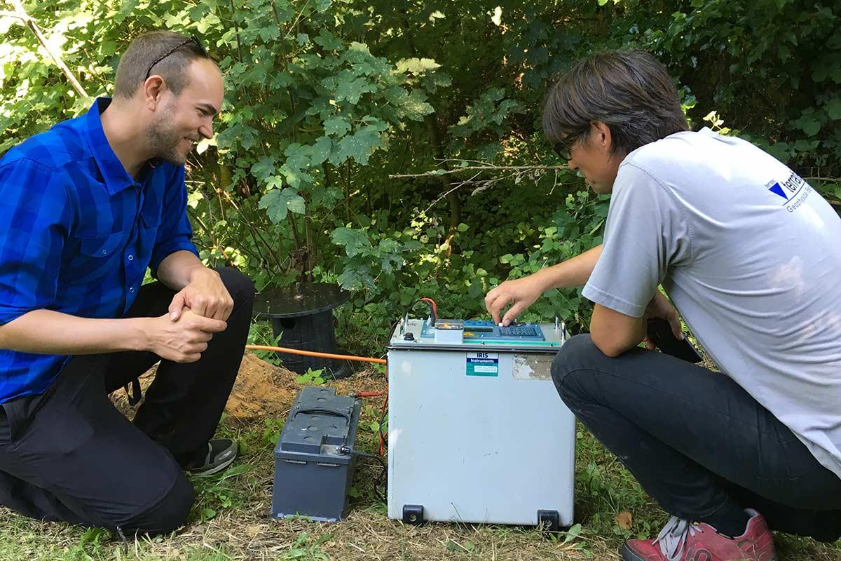 Lutz Capeller erklärt Tobis Vogt das Multielektrodenmessgerät zur Messung des elektrischen Widerstandes im Untergrund. Das Gerät wird mit einer Autobatterie betrieben. Bild: Nagra