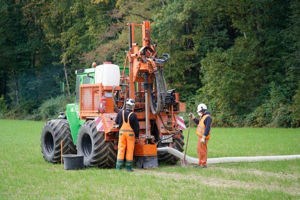 Auf dem Feld werden die Bohrlöcher für die kleinen Sprengladungen mit einem Bohrgerät erstellt, das auf einem Traktor montiert ist.