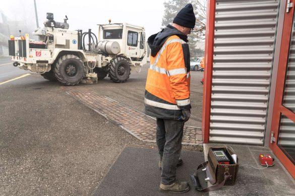 Mit dem Erschütterungsmessgerät kontrolliert ein Mitarbeiter des Messtrupps nahe am Gebäude, dass der Grenzwert für die erlaubte Bodenschwingung nicht überschritten wird.